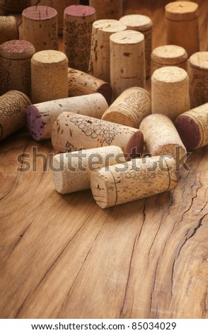 Different bottles used wine corks on wood - stock photo