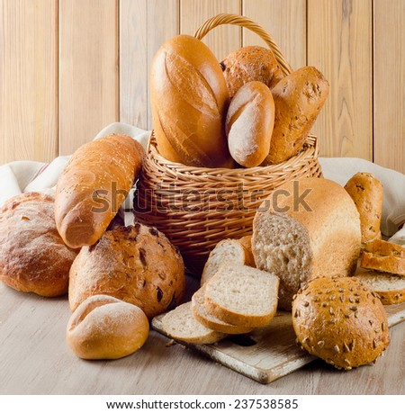 Different bread in basket  on a wooden background. Selective focus - stock photo