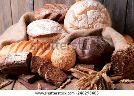 Different bread on table on wooden background - stock photo