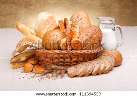 Different bread products with milk in jug on canvas