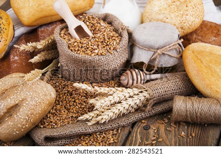 Different bread, wheat, milk and honey on the wooden table - stock photo