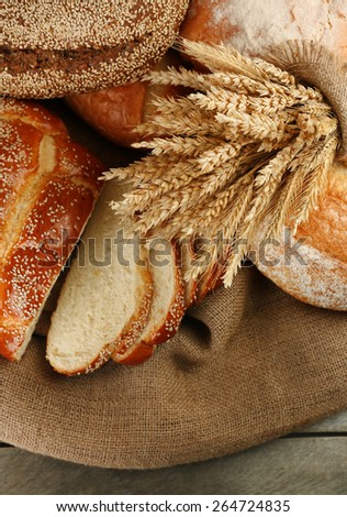 Different bread with ears on sackcloth background - stock photo