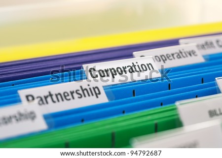 Different business organizations filed in colored folders, focus - stock photo