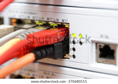 different cables plugged into high speed switch.  broadband, connectivity and data center concept - stock photo