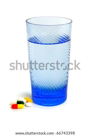different capsules with glass on white background
