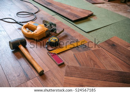different carpenter tools (rubber hammer, electrofret, joiner angle) on the laminated floor