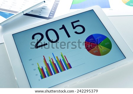 different charts with the economic forecast for 2015 in a tablet, on a desk full of charts - stock photo