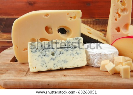 different cheeses served on wooding cutting board - stock photo