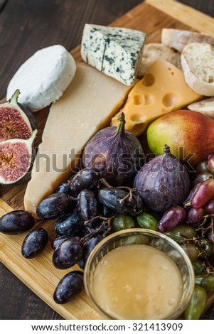Different chesse with honey, grapes, pear and bread