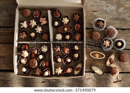 Different chocolate candies in paper box on wooden background, close up