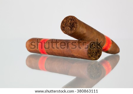 Different cigars on a  glass table and white background - stock photo