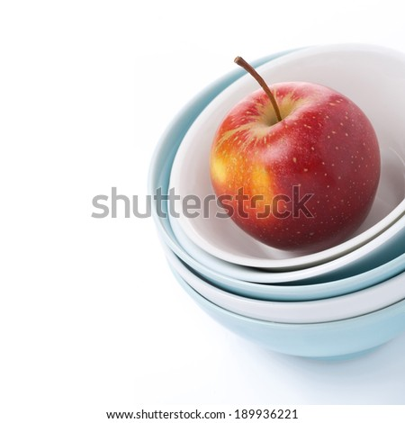 different clean bowl and red apple, close-up, isolated on white - stock photo