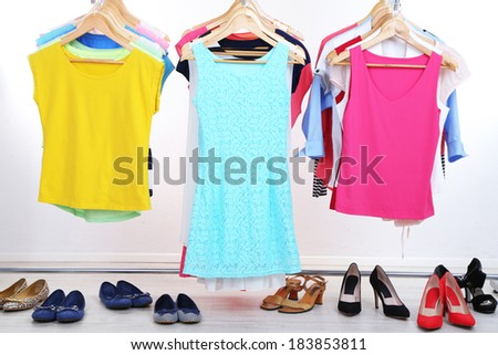 Different clothes on hangers and shoes on light background - stock photo