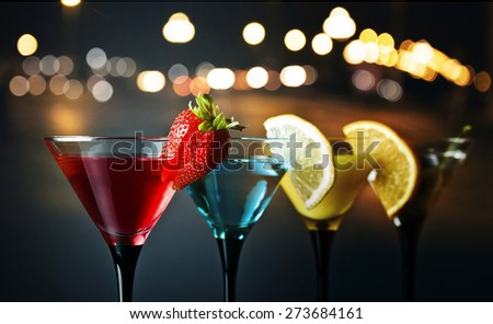 Different cocktails garnished with fruits , focus on foreground - stock photo