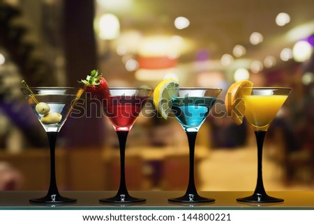 Different cocktails or longdrinks garnished with fruits - stock photo