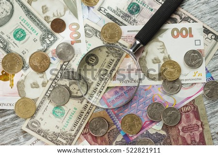 Different collector's coins and banknotes with a magnifying glass, wooden background