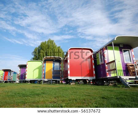 Different color caravans against blue sky - stock photo
