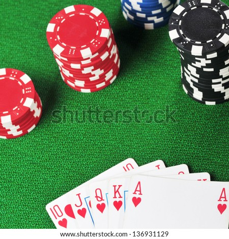 different color chips for gamblings and playing cards on green - stock photo