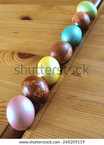 Different color easter eggs diagonal row on wooden table        - stock photo