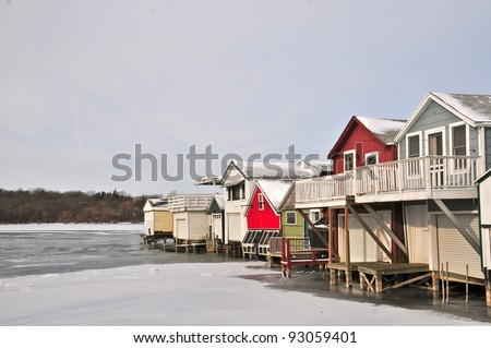 Different colored boathouses in a row rest on ice covered lake