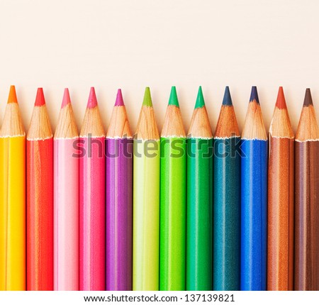 Different colored drawing pencils in a line on a white writing desk, over head view.
