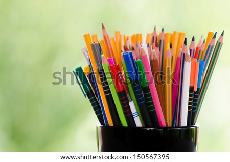 Different colored pencils against green background - stock photo