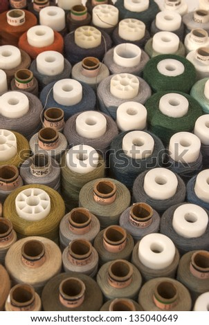 Different colored threads reels from above view as background
