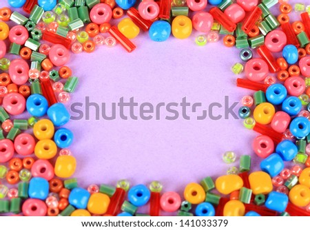 Different colorful beads on purple background - stock photo