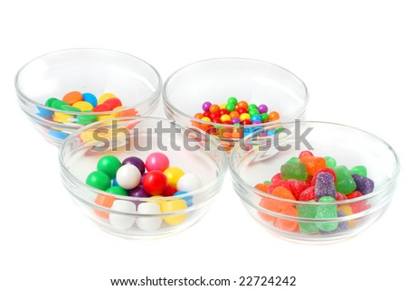 different colorful candy in clear dishes on a white background
