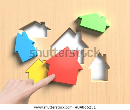Different colorful houses suit house shape holes of wooden board, with woman hand index finger pushing one to assemble.
