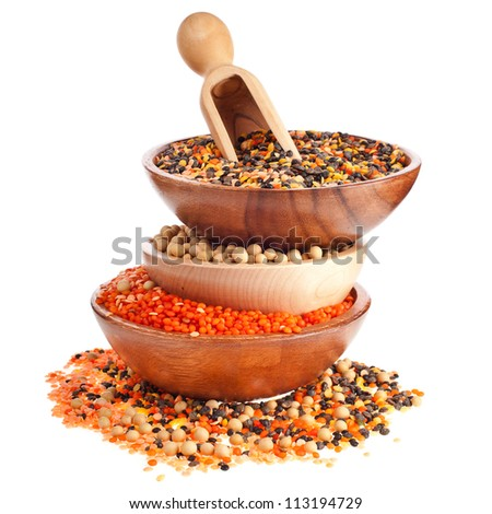 Different colorful lentils in a wooden bowl, soybeans and a scoop - stock photo