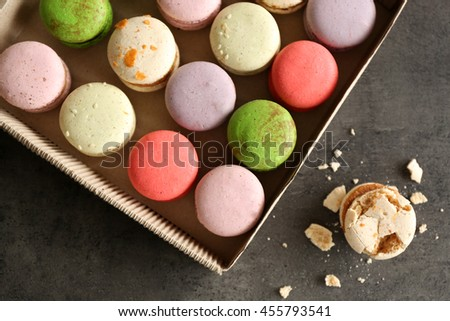 Different colorful macaroons in box on gray background - stock photo