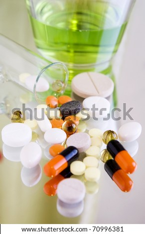 Different colorful pills and medicines on a mirror surface, close up, blur background, vertical - stock photo
