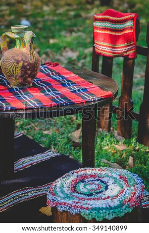 Different colorful rugs, carpets and ceramic jug for sale in a flea market - stock photo
