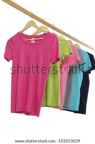 different colorful  t-shirt on wooden hangers - stock photo
