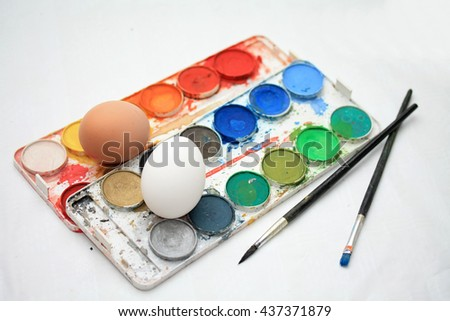 Different colors of paint, brushes and fresh eggs to make traditional easter decorations