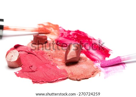 Different colors of smeared and sliced lipstick, lip gloss with brushes on white textured surface. Side view. Close-up
