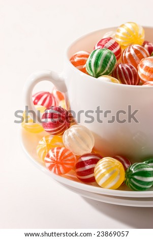 different colors of stripy lollipops on the white cup