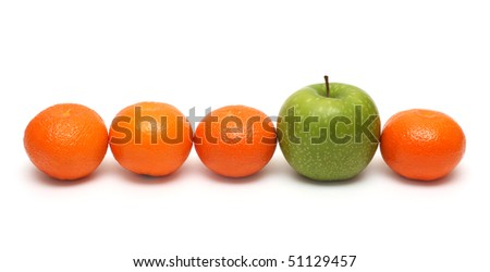 different concepts - green apple between mandarins - stock photo
