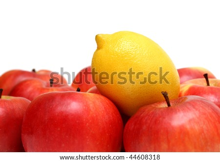 different concepts - lemon between red apples - stock photo