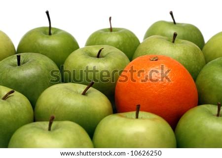 different concepts - orange between green apples - stock photo