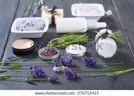 different cosmetic creams, bath salt, soap, anti aging serum pipette with fresh lavender flowers on black wooden texture - stock photo