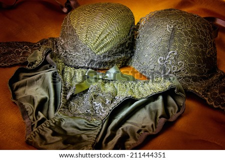 Different cup styles of lace bra with golden threads and pantie. Low key image. - stock photo