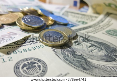 Different currency cash paper money dollars euros rubles with iron coins - stock photo