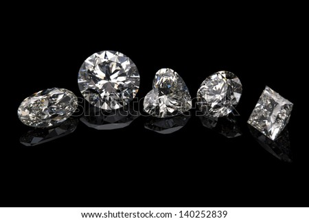 Different cuts of diamond isolated on black background. - stock photo