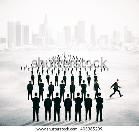 Different deirection concept with arrow shaped crowd of businesspeople going in one direction and just one person walking away on blurry cityscape background - stock photo
