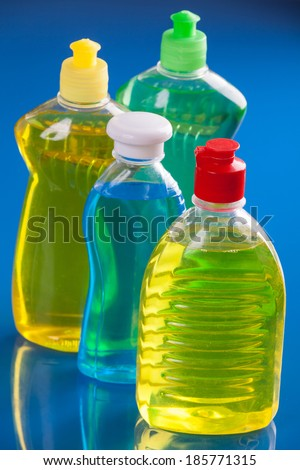 Different detergent bottles on white background on blue background - stock photo