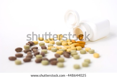 different drugs and health supplement pills from a medicine bottle on white background , selective focus , copy space. - stock photo