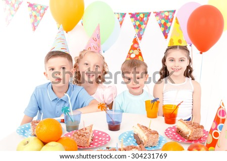 Different emotions. Group of little cheerful kids sitting at table during birthday party.