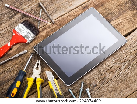 Different equipment tools of builder and tablet pc on wooden texture table - stock photo